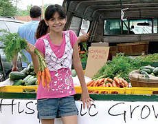 Hispanic Growers: Girl holding carrots