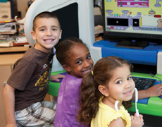 3 children working at a computer, smiling