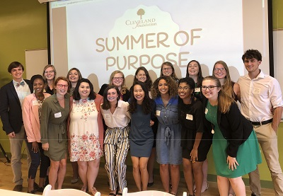 "Group of 2018 Summer Interns stands in front of ""Summer of Purpose"" backdrop"