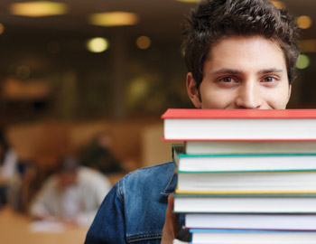 Male student holding large stack of textbooks