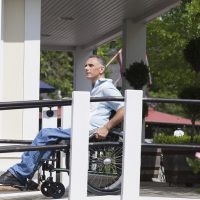 Man in wheelchair uses ramp to access building