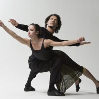 Two dancers from Malpaso dance troupe pose with outstretched arms