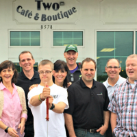 A group of people stand outside storefront for ribbon cutting of Two Cafe and Boutique opening