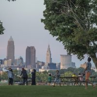A family playing together at Edgewater Park with Cleveland skyline in background