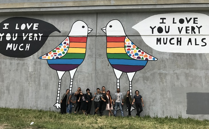 Malpaso Dance Company dancers pose in front of Kind Comments Instagram mural of two rainbow doves in Cleveland