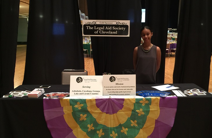 Caitly Reynoso stands behind Legal Aid Society information table at event