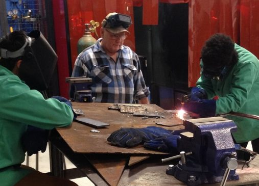 Gary Dudich, retired Journeyman Ironworker and Technical Corps Program Member assists welding students at Max S. Hayes High School with practice welds.
