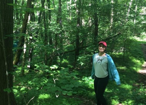 Maritess is pictured walking in the woods