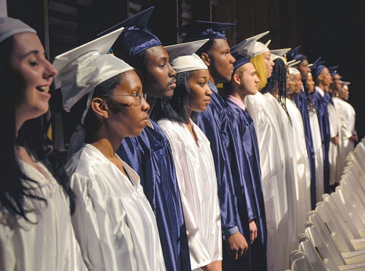High school graduates stand in a line dressed in their caps and gowns