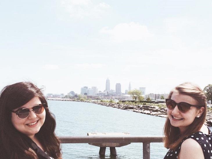 Katie and another girl stand in front of Lake Erie with Cleveland skyline in distance