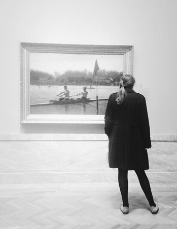 Katie Brennan stands in front of Thomas Eakins painting at Cleveland Museum of Art