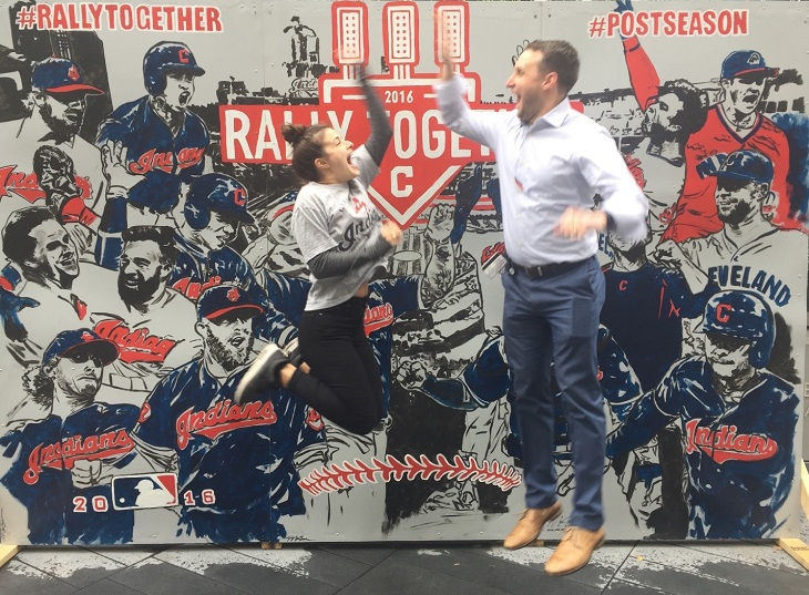 Tabitha and her brother jump and high-five in front of a Cleveland Indians mural