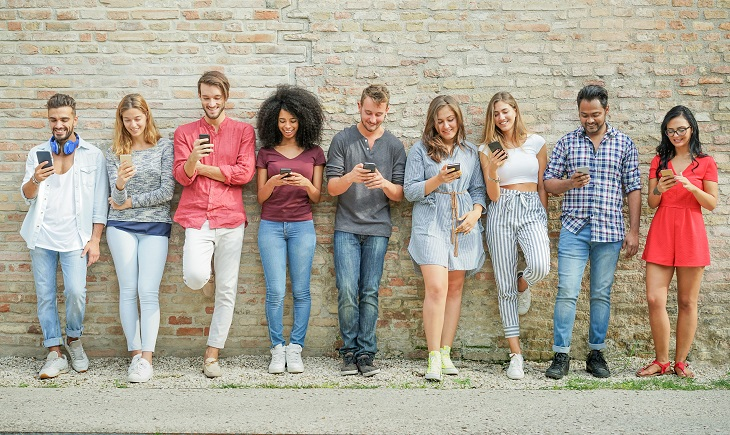Diverse group of people using mobile smartphone outdoors