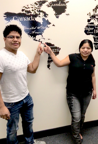 An immigrant man and women - Clara and Modesto - stand in front of world map