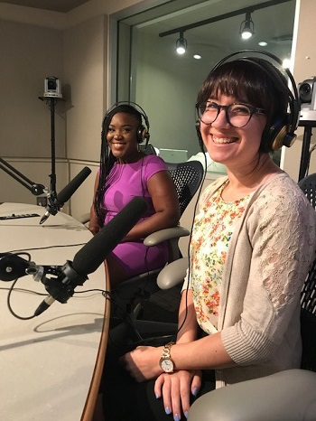 Two women sit in front of microphones while being interviewed on local radio station