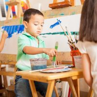 Three kids mixing paint and working on a painting during art class at school