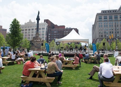 a crowd sits at picnic tables on public square listening to city club panel