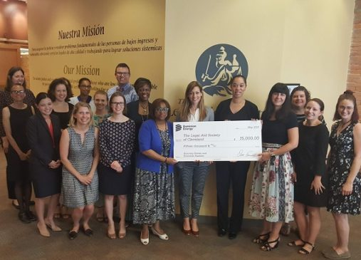 A group of people from the legal aid society pose for a group photo with a giant check