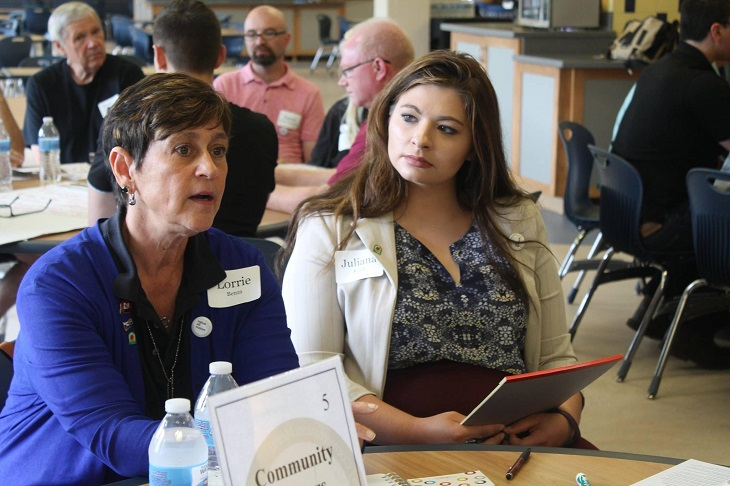 Juliana Kosik sits with another woman at a table during an event