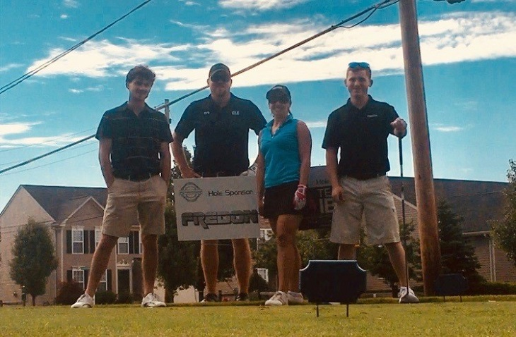 Nathan and three others stand on golf course with sponsor sign