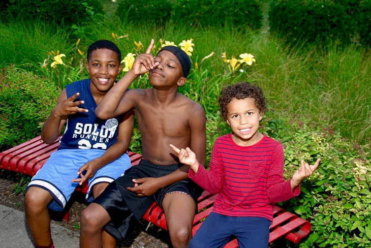 Three boys sit outside on a park bench