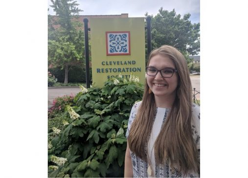 Katie stands in front of Cleveland Restoration Society sign
