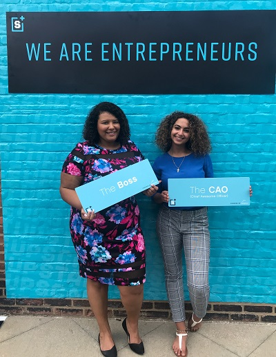 "Christina and colleague stand in front of blue wall that reads ""We are Entrepreneurs"""