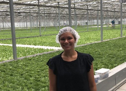 Caroline Carulas stands in front of rows of lettuce inside Evergreen greenhouse