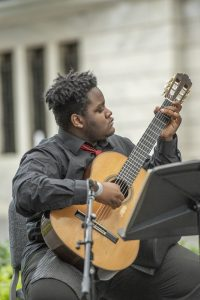 A mastery arts student performs classical guitar