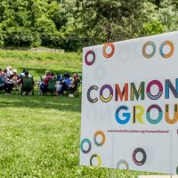 Image of Common Ground yard sign with group of people sitting in distance