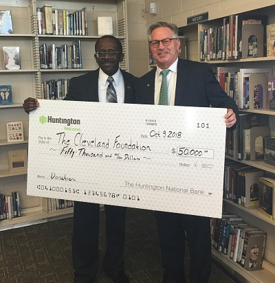 Leon Wilson of the Cleveland Foundation and a representative from Huntington Bank hold a giant check showing Huntington Bank's contribution
