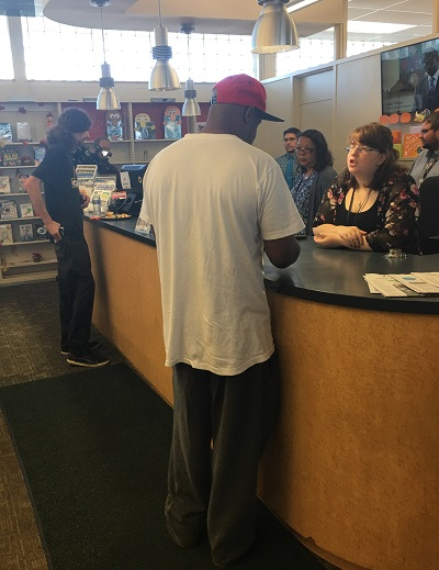 Two library customers check out materials at the circulation desk