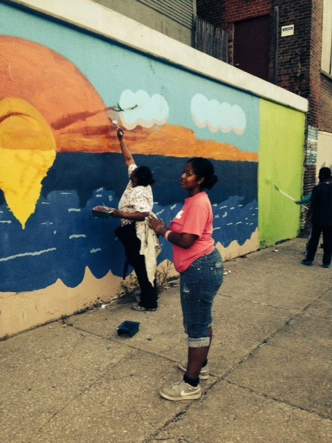 Two people stand in front of neighborhood mural