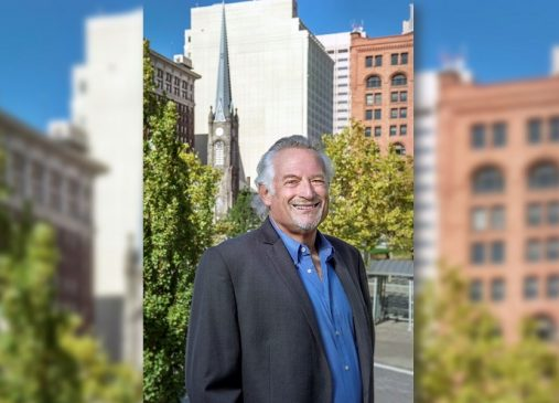 Ed Rivalsky stands outside in Cleveland Public Square with buildings in the background