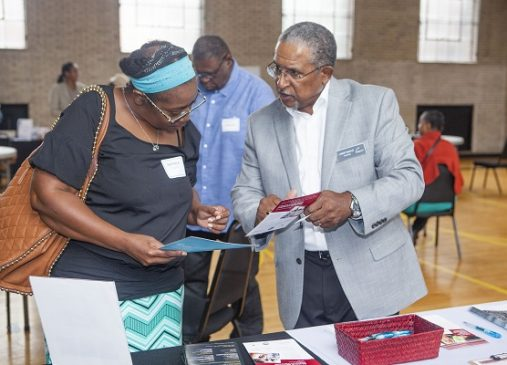 A man and a woman look through informational materials over a table