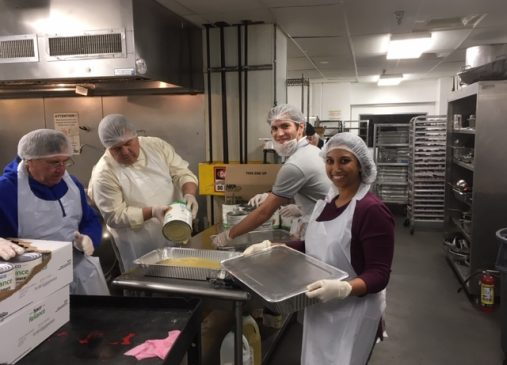 Four members of the Cleveland Club of Washington, D. C. transfer apple sauce from can to pan in the Club's effort to deliver balanced meals to Washington's hungry.