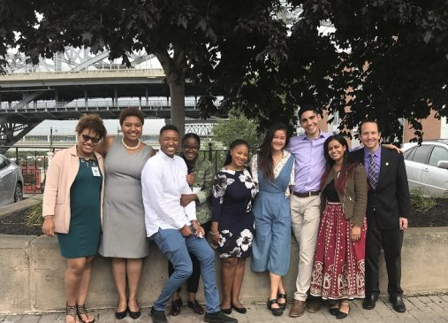 The 2017-18 Public Service Fellows pose for a photograph outdoors with their host site supervisors