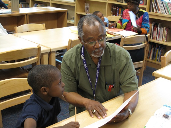 Larry Jemison works on reading skills with a student seated next to him