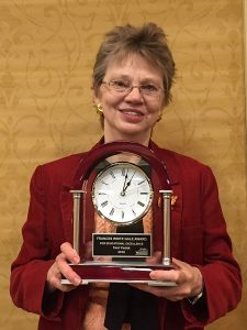 Terri Fedak stands with award