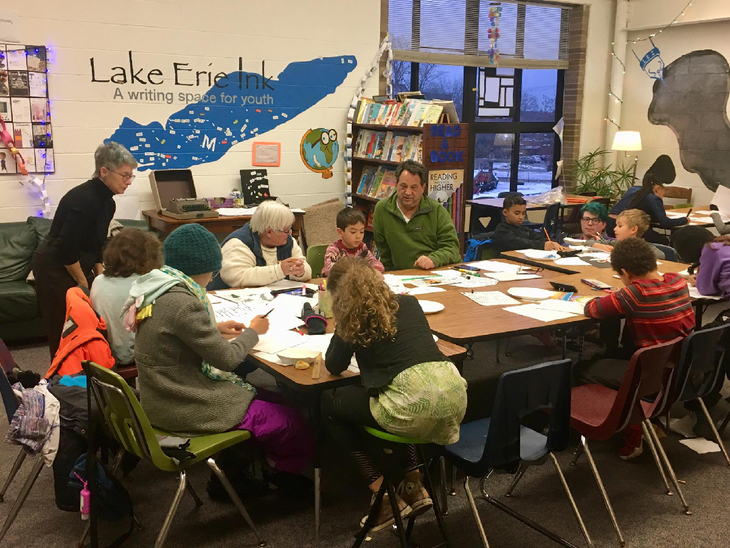 A group of students and instructors sit around a table at Lake Erie Ink