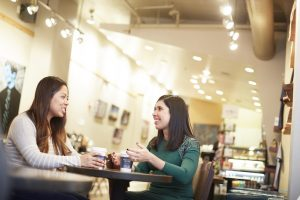 Two women sit together and talk with one another at a coffee shop