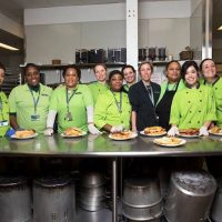 a group of women in chef jackets stand in commercial kitchen