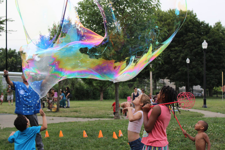 Children play with giant bubble wands in a park