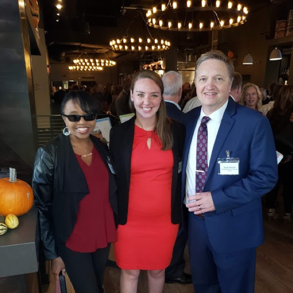 three people pose for a picture at an event