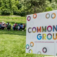 Common Ground yard sign with grassy field and group of people in the background