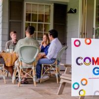 a group of people sit around a table on a porch
