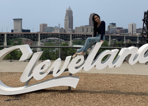 Meshal sitting on top of the Cleveland script sign with city skyline in background