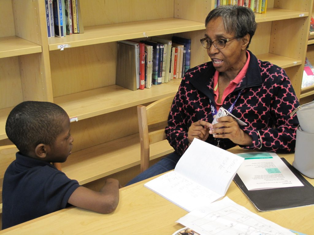 An older adult sits at a table working with a young student