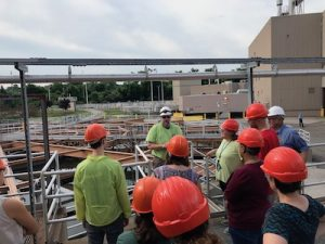 a group of people in hard hats tour a waste water treatment plant