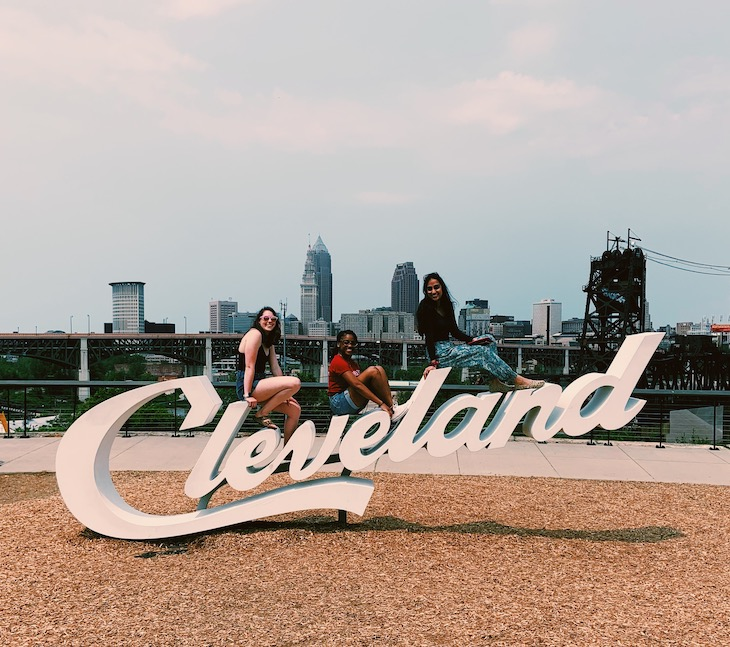 Maggie and other interns pose on the Cleveland script sign with skyline in background